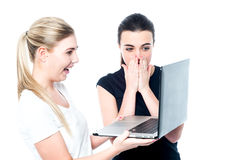 Excited girls watching videos on laptop Stock Photo