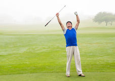 Excited golfer cheering on putting green Royalty Free Stock Images