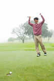 Excited golfer cheering on putting green Stock Photo