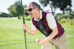 Excited golfer holding ball and club Royalty Free Stock Photography