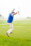 Excited golfer jumping up. On a foggy day at the golf course Royalty Free Stock Image