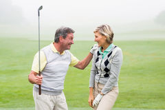 Excited golfing couple cheering. On a foggy day at the golf course Stock Photography