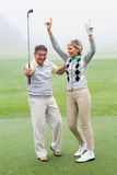 Excited golfing couple cheering. On a foggy day at the golf course Stock Photos
