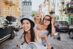 Excited and gorgeous friends are riding on one motorcycle. Chinese girl is smiling. She is wearing helmet. Her friends Royalty Free Stock Photos