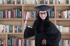 Excited graduate student in gown posing in library. Excited student wearing graduation gown posing in the library Stock Image