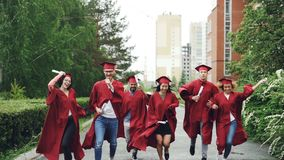 Excited graduating students running along road on campus holding diplomas wearing graduation clothes gowns and hats