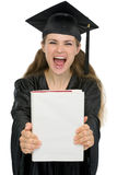 Excited graduation girl student showing book. Isolated on white Royalty Free Stock Photography