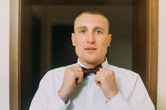 Excited groom adjusting his bow tie looking at camera. Indoor shot of wedding morning Stock Photo