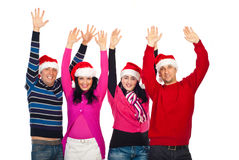 Excited group of friends with Santa hats. Four excited  people friends wearing Santa hats and colorful clothes and standing with arms up and laughing together Royalty Free Stock Images