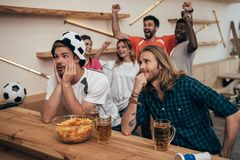 excited group of multicultural friends celebrating and watching soccer match at bar with beer royalty free stock photos