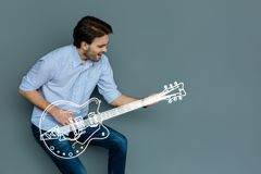 Excited guitar player practicing his new song and smiling. Favorite guitar. Cheerful emotional young musician playing the guitar and practicing his new wonderful Stock Image