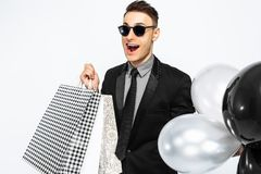 An excited guy in a black suit and sunglasses, with shopping bag