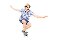 Excited guy with cap and sunglasses skating on a skate board Royalty Free Stock Images