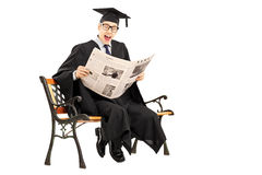 Excited guy in graduation gown reading a newspaper seated on ben Stock Photo