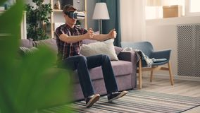 Excited guy is having fun with augmented reality glasses wearing headset and playing racing game moving hands and legs. Expressing positive emotions on sofa at stock footage