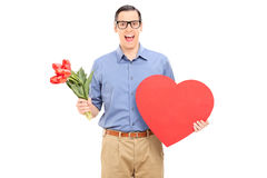 Excited guy holding red heart and bunch of flowers Stock Image