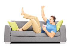Excited guy lying on a sofa and listening music Royalty Free Stock Image