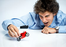 Excited guy plays with red toy motorcycle Stock Photography