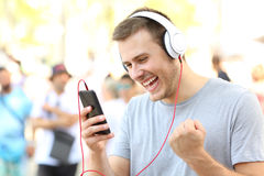Excited guy receiving good news on phone. Excited guy receiving good news on a mobile phone on the street stock images