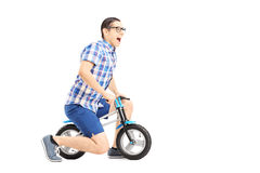Excited guy riding a small bicycle Royalty Free Stock Photos