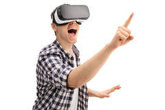 Excited guy using a VR headset. And touching something isolated on white background Stock Photos