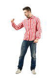 Excited guy yelling in casual clothes with clenched fist. Young excited guy yelling in casual clothes with clenched fist. Full body length portrait isolated over Stock Photography