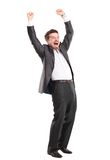 Excited handsome business man with arms raised in success Stock Images
