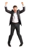 Excited handsome business man with arms raised in success Royalty Free Stock Images