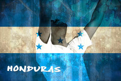 Excited handsome football fan cheering. Against honduras flag in grunge effect Royalty Free Stock Photo