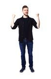 Excited handsome man with arms raised in success Stock Photos