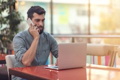 Excited happy bearded freelancer reading email with results about victory in modern online contest sitting at laptop royalty free stock photography