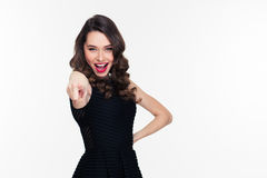 Excited happy confident curly retro styled woman pointing at camera. Excited happy confident curly retro styled young woman in black dress pointing at camera Royalty Free Stock Photo