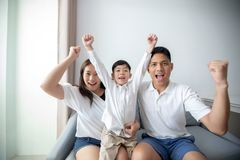 Excited and Happy family with arms raised while watching television at home stock image