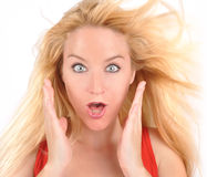 Excited Happy Girl with Long Hair Blowing. A closeup of a young girl looks excited with her blond hair blowing fast on a white background and hands up on her Stock Photos