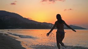 Excited happy girl wearing bikini running in tropical beach at sunset in slow motion. 1920x1080 stock footage