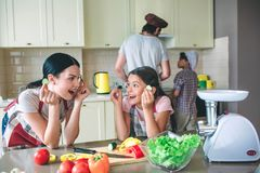 Excited and happy girls are leaning to table and looking at each other. They play with round pieces of cucumber. Girls royalty free stock photos