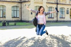 Excited happy joyful female student jumping with book in her han. D and triumphing because of passing the exams Royalty Free Stock Photos
