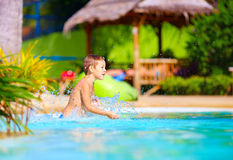 Excited happy kid boy having fun in pool, summer vacation Stock Images