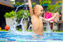 Excited happy kid boy jumping in pool, water fun Stock Photos