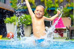 Excited happy kid boy jumping in pool, water fun Royalty Free Stock Image
