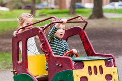 Excited happy kids driving a toy car Royalty Free Stock Photography