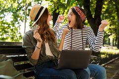 Excited happy ladies friends outdoors sitting using laptop computer. stock images
