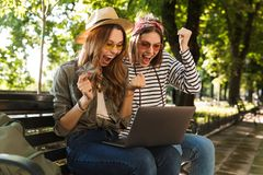 Excited happy ladies friends outdoors sitting using laptop computer. royalty free stock photo