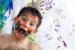 Excited happy little boy doing finger painting Stock Photo