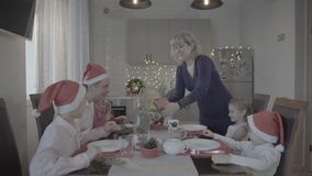 Excited happy lovely family of six celebrating Christmas dinner in festive atmosphere cozy kitchen. Happy lovely excited family of six celebrating Christmas stock footage