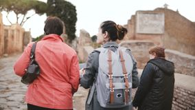 Excited happy mixed age European tourist women explore old historic ruins in Ostia, Italy, look at smartphone photos. stock video footage