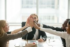 Excited happy multiracial business team giving high-five at offi stock photo
