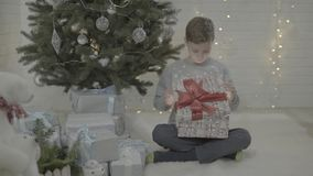 Excited happy small boy child opening christmas present gift box in decorated new year tree festive atmosphere room stock video footage