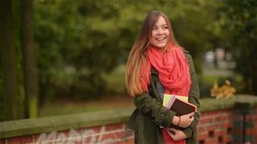 Excited happy student girl smiling joyful and blissful holding books outside in colorful fall park stock video
