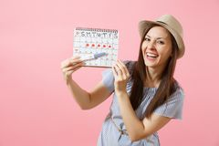 Excited happy woman in blue dress, hat hold in hand pregnancy test, periods calendar for checking menstruation days. Isolated on pink background. Medical stock images